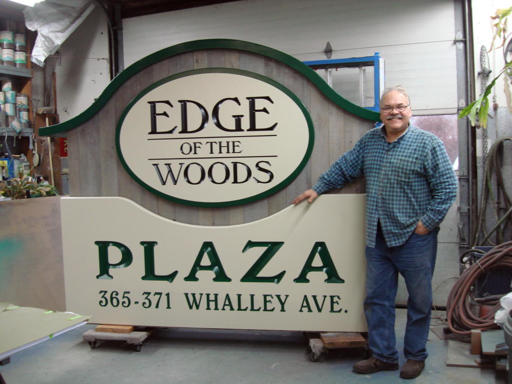 John Miller in front of top half of sign for Edge of the Woods in New Haven